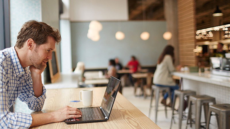 A man sitting in a coffee shop and browsing on his laptop.
