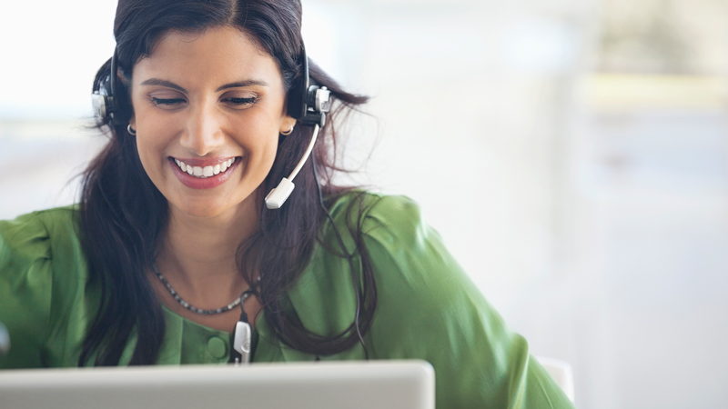 Woman wearing a headset using a laptop.