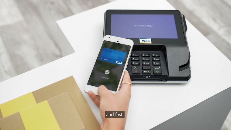 Hand holding a mobile phone , tapping mobile contactless Visa credit card on a payment terminal. Caption that says : and fast.