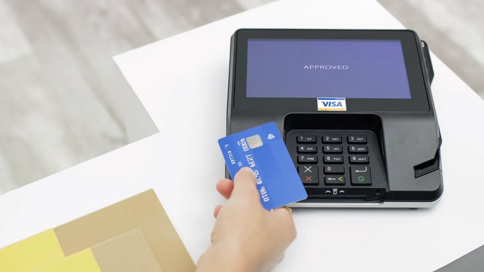 Person holding a Visa card at a contactless payment terminal.
