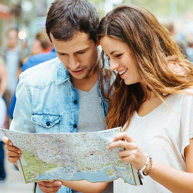 Couple looking at a map for directions in a busy street